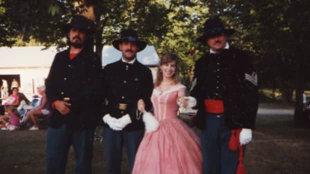 This was taken in Nova, OH, in July 1993. The first reenactment I ever attended in dress. The ballgown was bought at a theater sale for, I think, $15. With me are the gallant lads of the 7th Ohio Volunteer Infantry.
