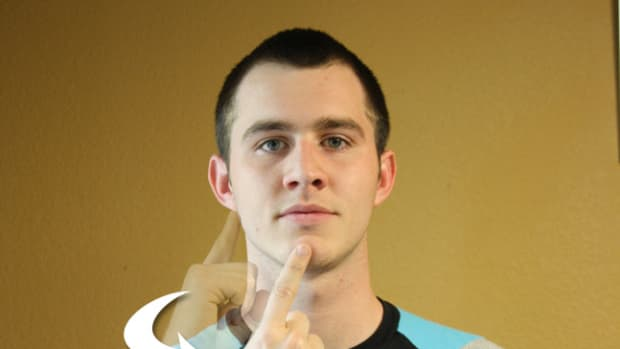 Index finger points starting at the ear and ending at the mouth or vice versa.