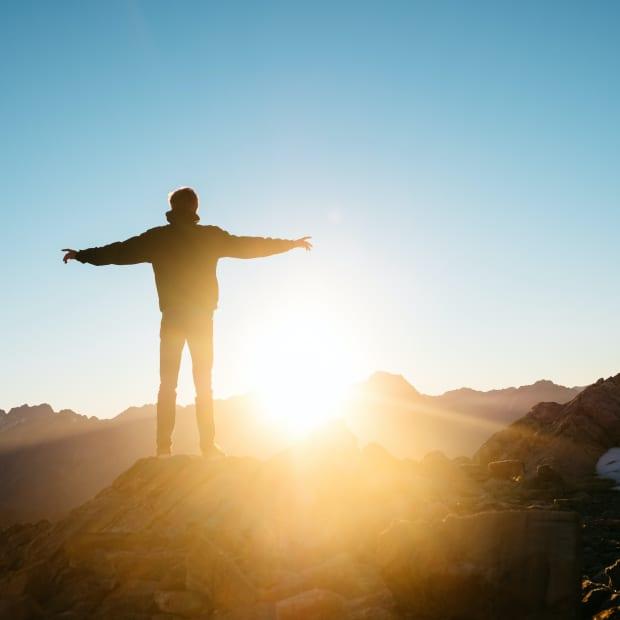 Person admiring sunrise on mountain