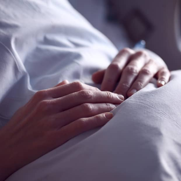 person laying in hospital bed with their hands over their stomach