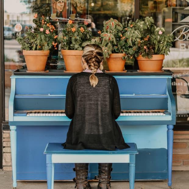一个女人在旁边用植物弹钢琴