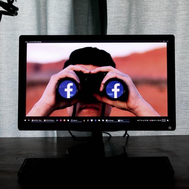 man using binoculars with the facebook logo on desktop computer screen