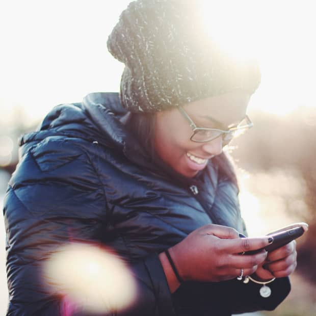 woman smiling at her smartphone