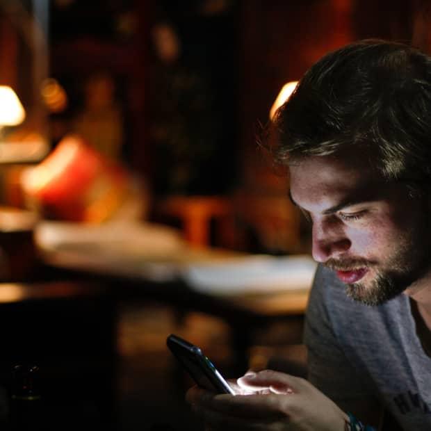 man frowns at his smartphone at night