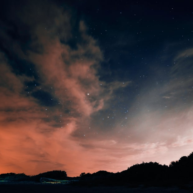 blue and orange night sky with clouds and stars