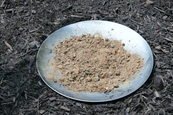 I buried the metal basin of a broken birdbath in a flowerbed and filled it with a few handfuls of sandy soil.
