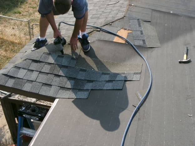 Laying the shingles.  The worker is standing on the garage roof, with the deck roof coming toward the camera.