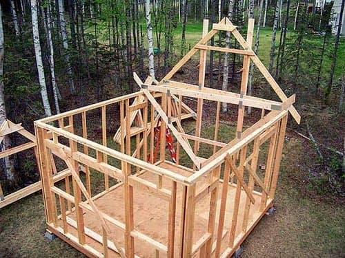 Bring the trusses inside and lift them upside-down—setting them on top of the wall.