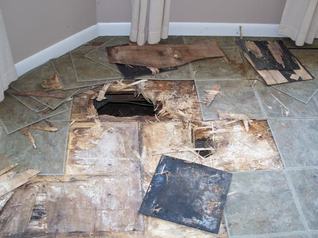BEFORE - Kitchen floor was damaged with holes through it. The tile was green and gray.