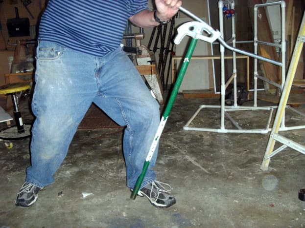 """Note how the bender handle is """"caught"""" with the users foot and leg.  It is common for the handle to slip on the floor and kick out, ruining the bend and possibly causing injury if it isn't held somehow."""