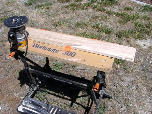 """The workpiece is clamped (with the orange """"dogs"""") onto a workmate bench."""