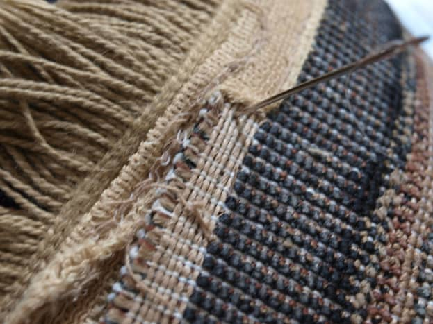 Begin on the back side of the rug and insert the needle.