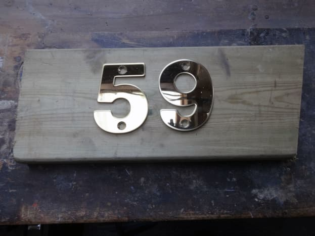 New brass house numbers test laid on decking offcut