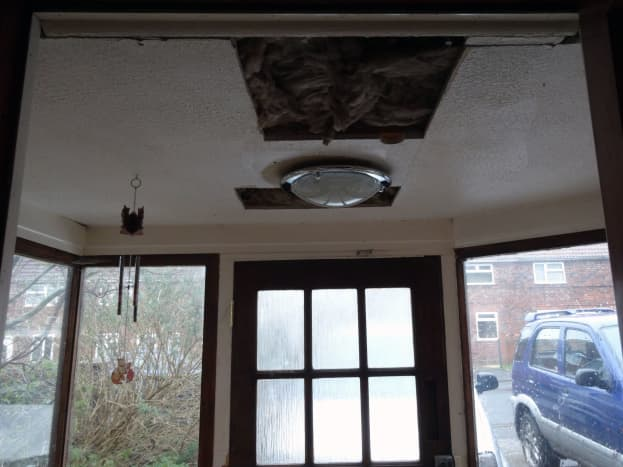 Cutting access holes in the ceiling to add 6 inches of insulation.