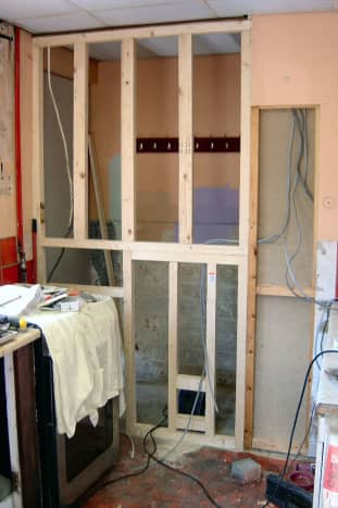 Building of the stud wall in front of space where the old back door was; space behind stud wall then utilised as a cloakroom, with access from the living room.