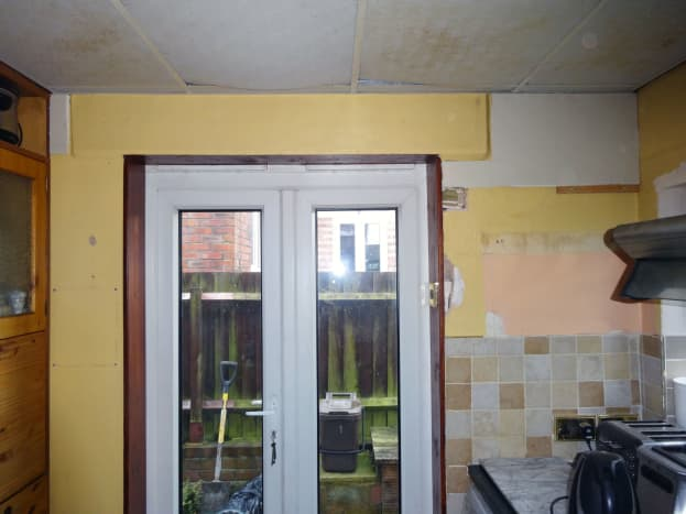 Plasterboard fixed to the wall on both sides of the door to level it with the lintel.