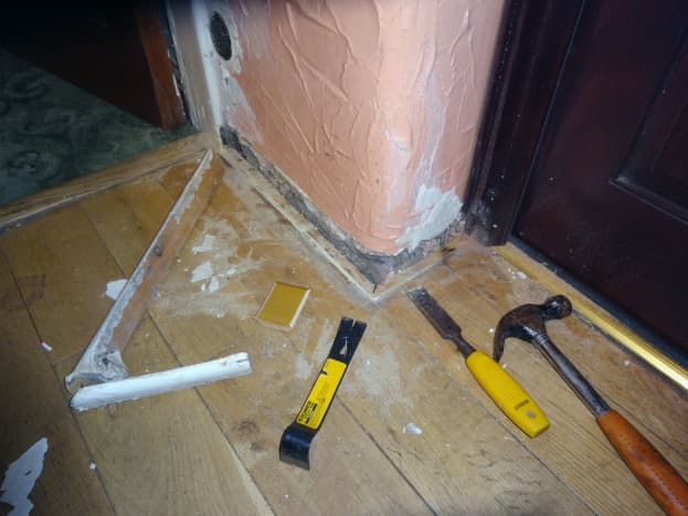 Old skirting board removed from base of wall between living room and porch doors; showing the extent to which the corner of old skirting board jutted out due to the corner of the wall being so prominently rounded