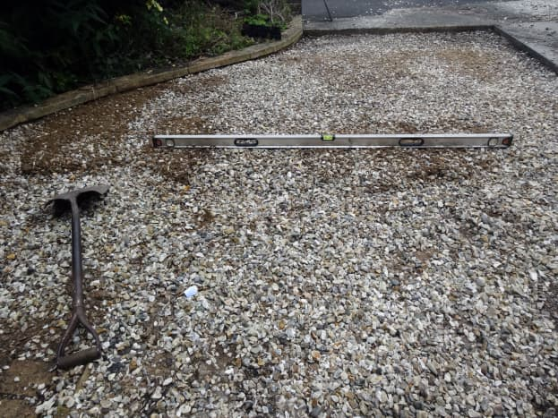 Using spirit level and shovel to level the gravel.