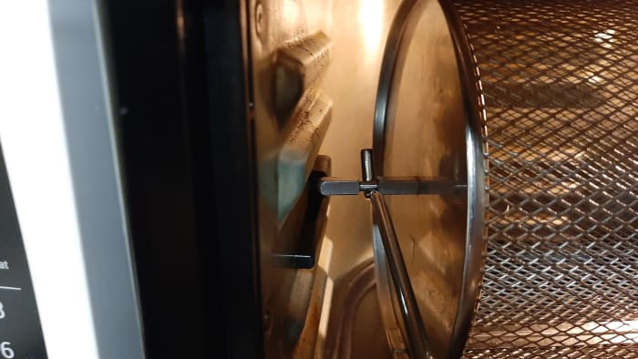 The left end of the rotisserie basket that attaches to the rotisserie mechanism. Slide it straight in. Do this step before doing the right side.