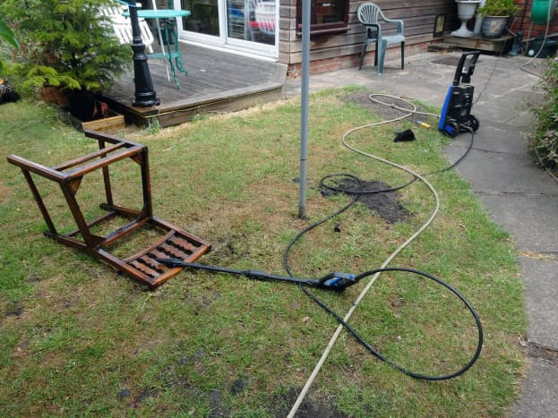 Pressure washer and chair on lawn, with pressure washer attached to outside tap.