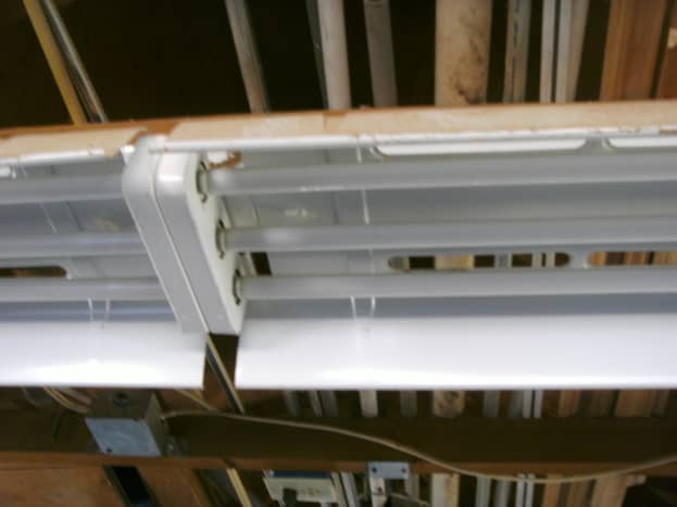 This fixture needs the entire reflective shield removed. One of the two plastic clips (on near each end) is shown here.