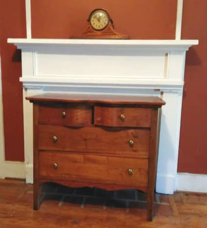 Dresser in front of closed off fireplace