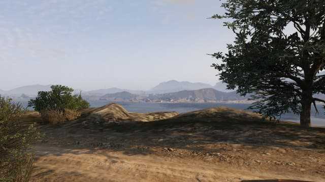 The overlook by the left side of the dirt road. Take position here.