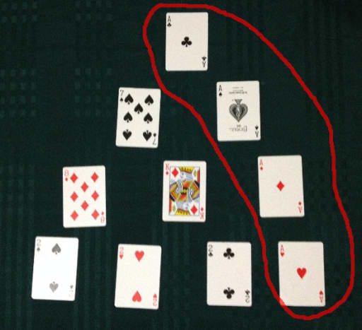 Four of a kind pattern with four aces. The player would place new cards over these aces. If the player is batting, they score an extra six runs.  If the player is bowling, they take a wicket.