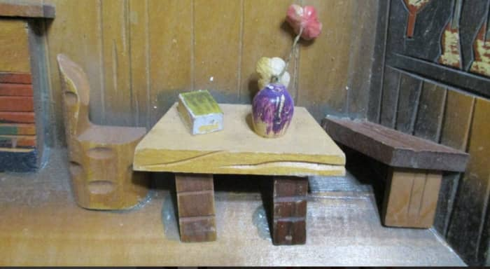 Vase on table, fabric flower, wire stem, painted, clay vase, book, table legs.