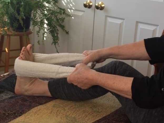 Soleus stretch. Bend the knee and pull back on the towel until you feel a pull in the back of your leg, just above the heel.