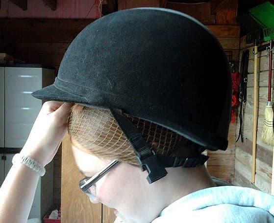 Step nine: Put helmet on over the hairnet back to front.