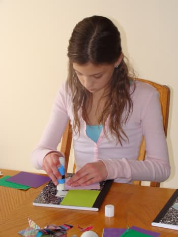 Olivia glues down her pictures.