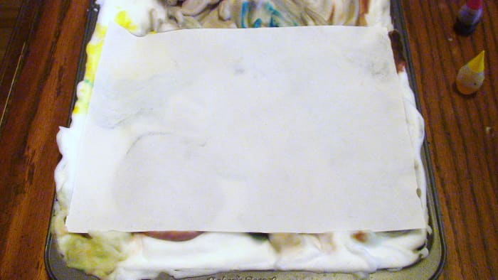 Printer paper is placed over top of the shaving cream and pressed firmly.