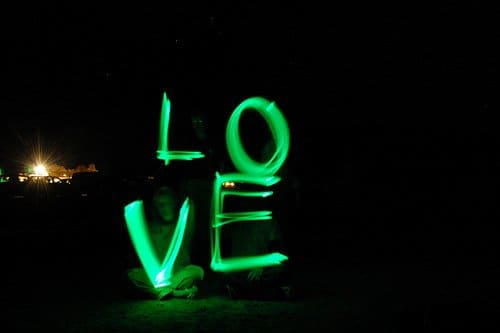 """Taking a picture while spelling """"love""""  with glow sticks."""