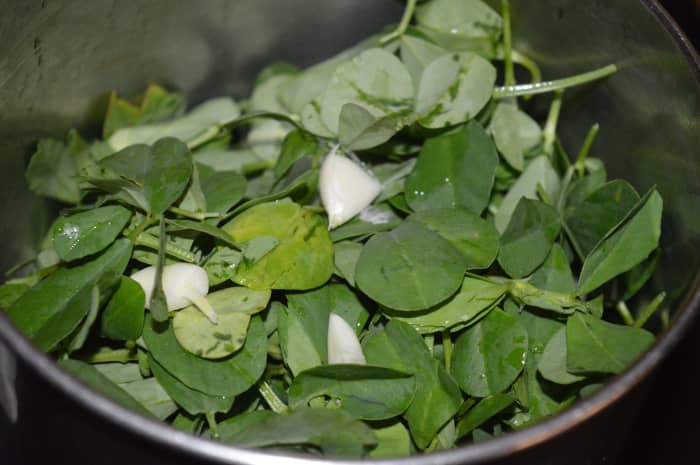Put the washed fenugreek leaves, garlic cloves and salt in a mixer grinder and crush them.
