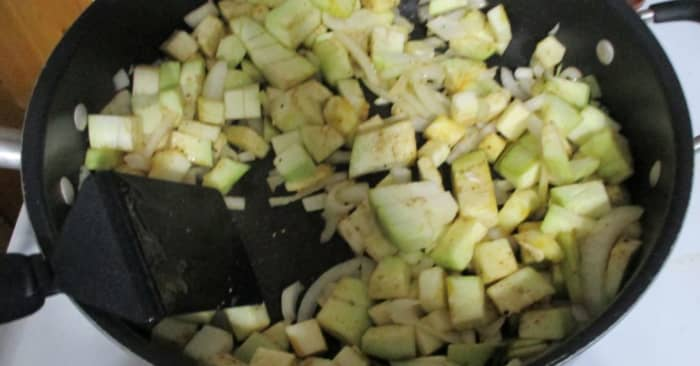 Add eggplant to onions. Stir to coat with oil.