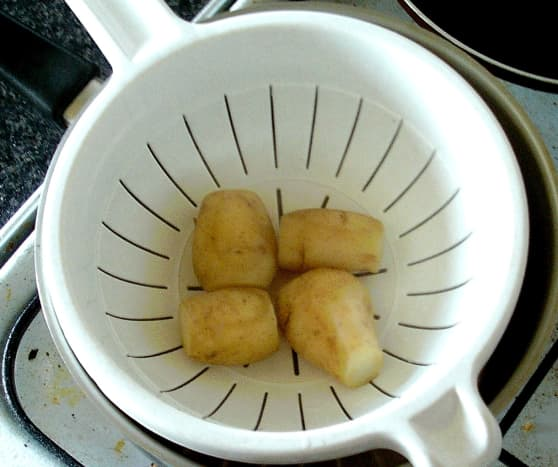 Trimmed potatoes are firstly parboiled and left to cool.