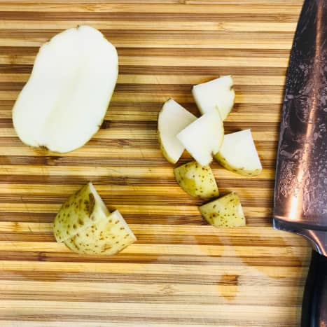 Slice the potatoes in half lengthwise and then in half again. Cut into even chunks about 1 inch in size.