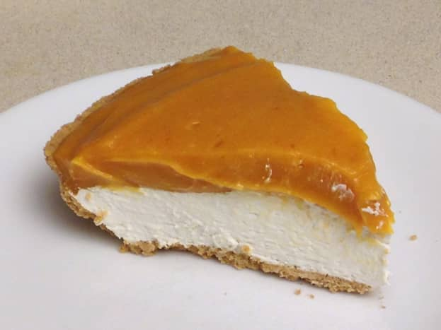 Serving of layered pumpkin pie with cream cheese layer topped with pumpkin-pudding layer