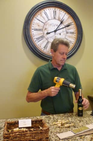 Wayde using heat to shrink the capsule around the just filled bottle of EVOO that we were purchasing from Olive & Vine.