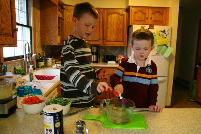 My two young sons add sage and salt to the chicken bullion.
