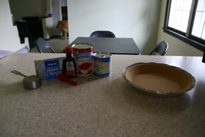 The ingredients for cherry cheesecake: cream cheese, condensed milk, lemon juice, vanilla, and cherry topping.