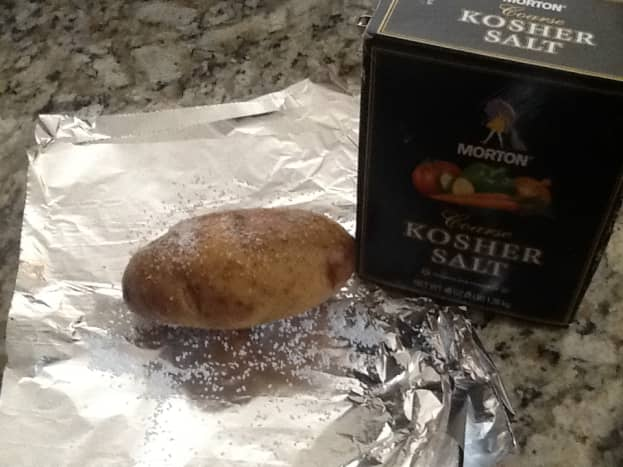 Sprinkle the scrubbed potatoes with Kosher salt and wrap them in foil.