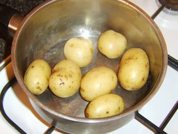 Boiled potatoes are drained and left to cool