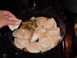 Layering cooked pierogi in baking dish.