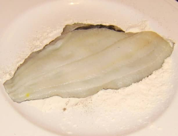 Skin side of plaice fillet is patted in seasoned flour