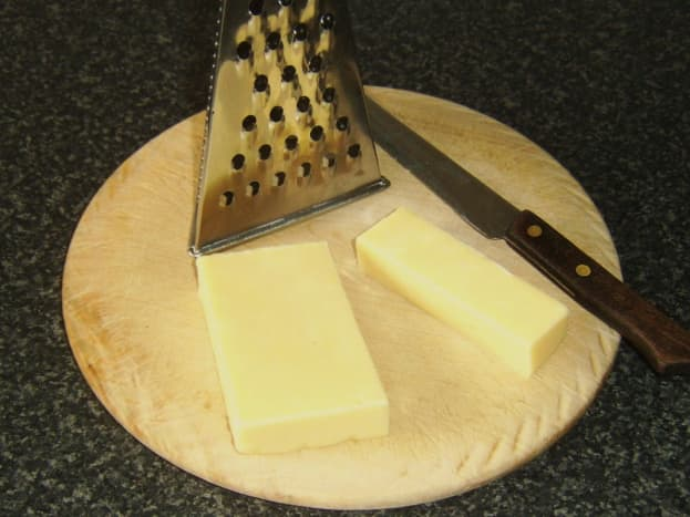 Wedge of cheddar cheese is cut for grating