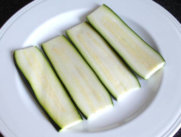 Zucchini slices are salted and set aside