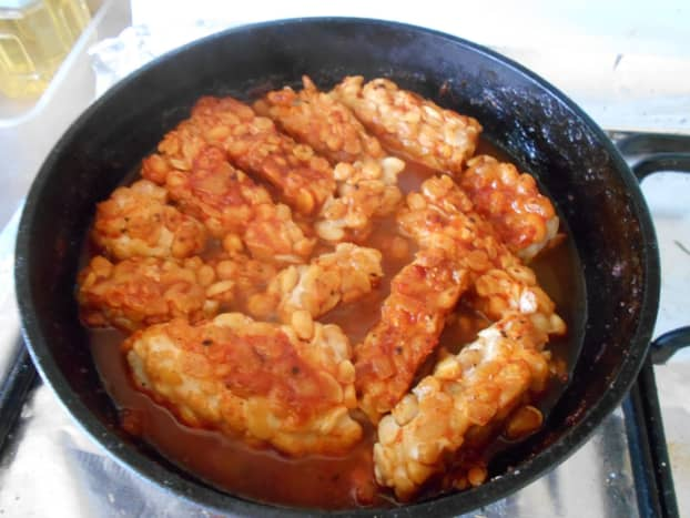 Soy tempeh simmering in tomato and chili sauce.