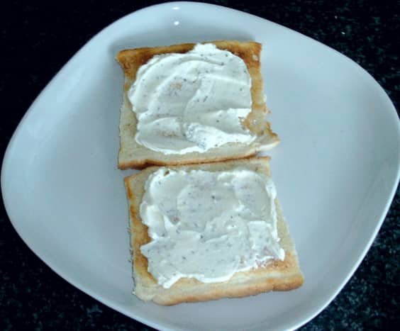 Cream cheese is spread on toast